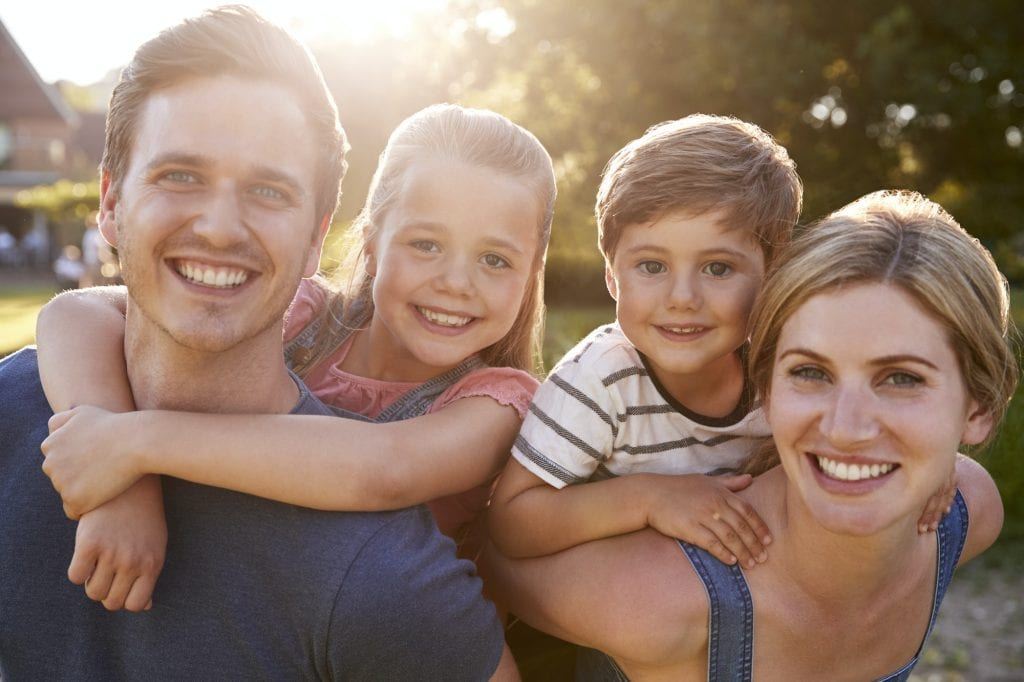Portrait Of Smiling Family Outdoors In Summer Park Against Flaring Sun